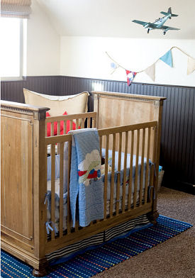 Jet airplane baby nursery theme with vintage decor and navy blue wainscoting and applique crib quilt
