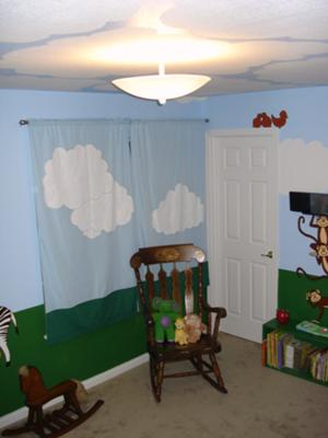 The homemade nursery curtains have hand-painted clouds to match the blue sky in the jungle theme nursery wall mural