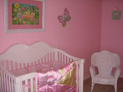 Joy's baby crib and nursery rocking chair with her pink Winnie the Pooh Crib bedding set.