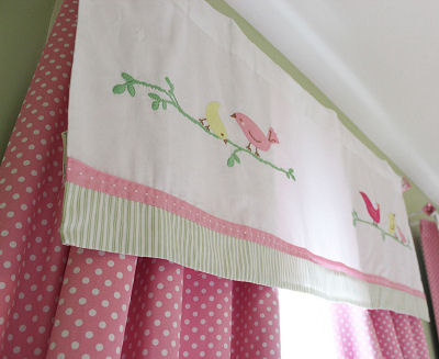 Pink and white curtain panels with polka dots and a window valance topper with bird appliques