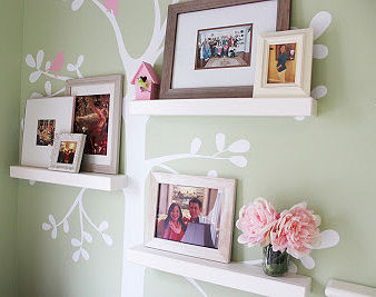 Family photos displayed on shelves in the branches of a tree nursery wall mural