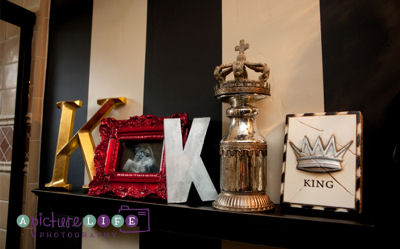 King themed decorations arrangement on a shelf in the baby boy nursery room with painted wall stripes