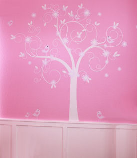 Large vinyl tree wall decal on the walls of a pink baby girl nursery with flowers and birds