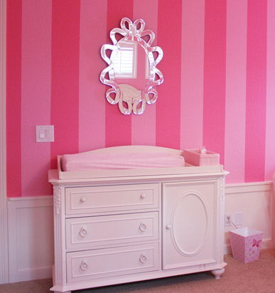 Antique dresser changing table in a pink baby girl nursery room