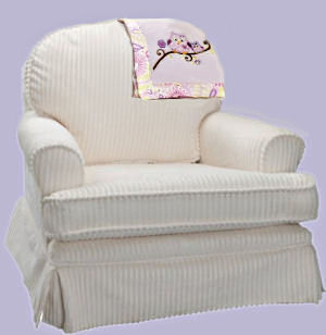 Comfortable chair for a baby nursery upholstered in soft cream color chenille fabric