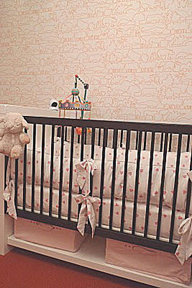 Pink orange and white baby girl nursery room with a modern Maclaren Netto crib and Porthault linens