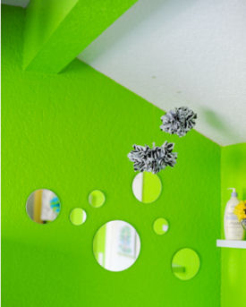 Lime green baby nursery walls with an arrangement of mirror decorations