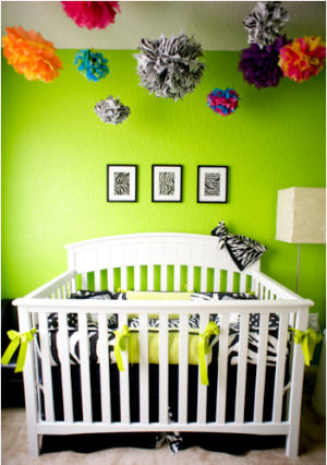 Custom zebra print baby crib bedding set with personalized pillows in a nursery with lime green wall paint color