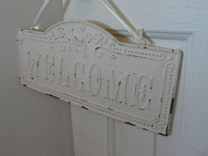 A chipped white painted vintage welcome sign on the door to a baby girl shabby chic nursery in pink gray and white