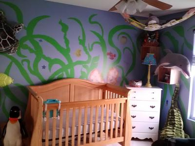 DIY under the sea ocean creatures nursery wall mural painting and a natural wood color baby crib that is close to the color of seashells.