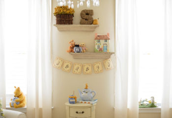 Vintage Winnie the Pooh collectibles on display in the baby's nursery
