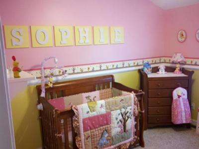 The yellow wall letters spell out Sophie's name.  The pink wall paint color of her Winnie the Pooh theme nursery is the perfect background for them.