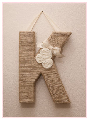 Baby girl nursery wall initial letter K wrapped in twine decorated with fabric ivory rosettes