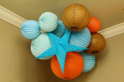 The aqua blue, brown and orange star and orb paper lantern nursery ceiling cluster reflects the color scheme of Baby J's room.