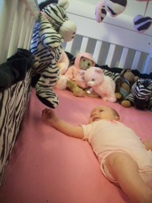 Our baby girl playing in her pink zebra crib