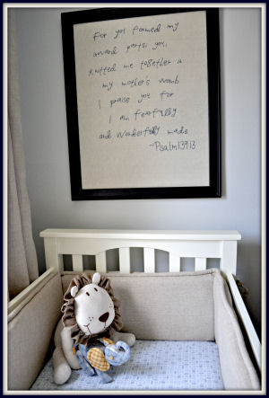 Framed embroidered Bible verse displayed over the crib in Owen's baby nursery room