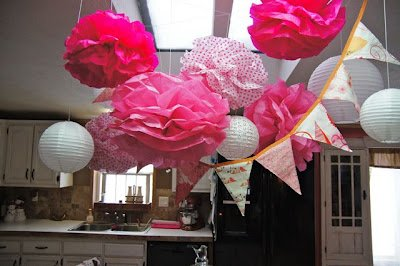 Pink and white tissue paper pom poms and party banner for a baby girl butterfly theme shower
