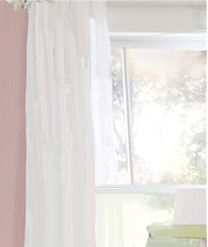 Sheer white curtain panels in a pink baby girl nursery room