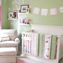 Pink and green baby nursery with tree wall decal and family photos on floating wall shelves