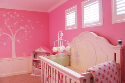 Pink baby girl nursery with striped walls, ruffled fuschia curtains and polka dot sheers.