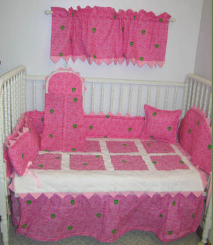 Pink white and John Deere green baby nursery bedding set with crib quilt and window valance curtains for a girl room