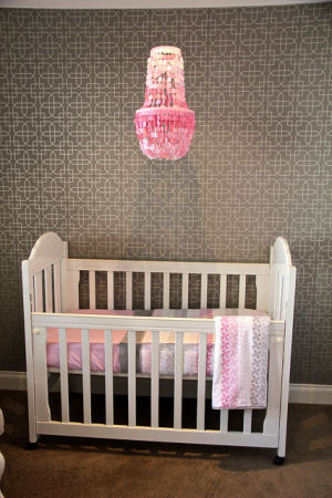 Pink capiz shell nursery chandelier in a modern pink and gray baby girl nursery room with gray and white geometric pattern wallpaper