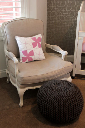 Pink and white square accent pillow in the seating area of a baby girl nursery room