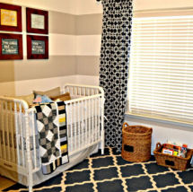 This modern baby boy nursery features gray and white wall stripes and chevron fabric patterns