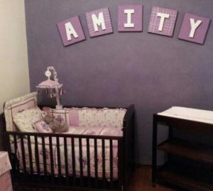 A small baby girl nursery with a purple accent wall