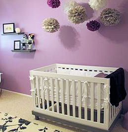 Modern urban style purple and black baby girl nursery with a tattoo theme and crib set