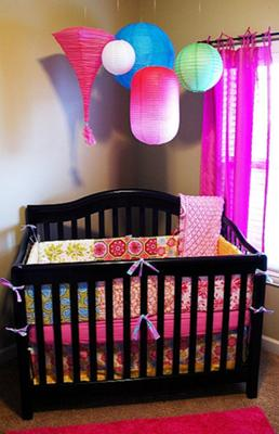 Colorful paper lanterns hung from the ceiling over the crib reflect the bright colors of the custom baby bedding.