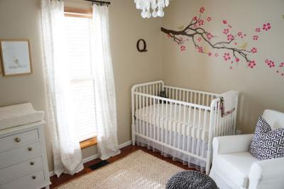 This baby girl's raspberry pink and gray nursery has an elegant and airy atmosphere including golden birds perched on branches and elements that make the room comfortable and cozy.