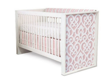 Pink and grey baby girl crib bedding set in an elegant crib with woodworking cut outs details carved