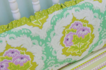 A baby girl's bedding set with ruffles in orchid purple, emerald green and gold.
