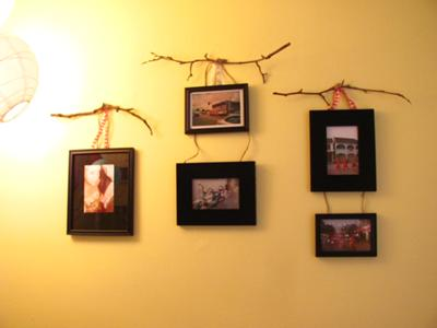 A collection of framed black and white photographs displayed using tree branches and ribbon picture hangers that I made myself!
