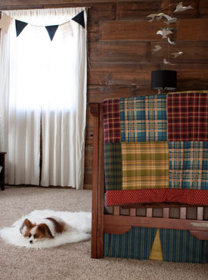 A rustic crib in a baby boy nursery room with a beautiful homemade patchwork crib quilt