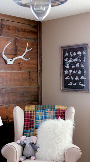 Rustic nursery ideas with reclaimed wood wall deer antlers decor and a comfortable rocking chair