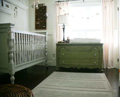 A silver gray baby crib and olive green dresser in a nursery with mint green walls