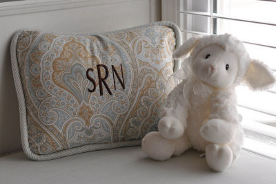 A plush stuffed toy and a personalized monogrammed pillow to match the crib set
