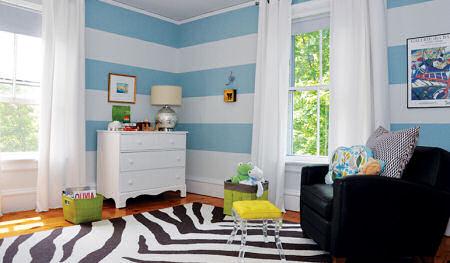 A baby boy nursery room with black and white zebra rug and black leather nursery glider
