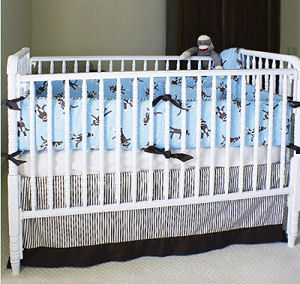 Sock monkey baby crib bedding set with a baby blue, brown and red quilt and fitted crib sheets and striped mattress ticking bed skirt with gray stripes in a neutral nursery