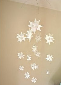 Star theme baby crib mobile with white paper origami stars hung on a wire frame