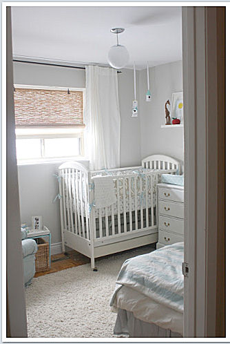 The serene, light blue brown and greige baby boy nursery room features unique storage features without sacrificing style