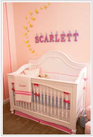 White crib with personalized quilt and Pottery Barn Kids baby bedding set in a vintage girl nursery