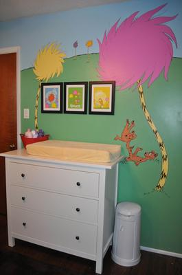 The baby's nursery wall is painted with a colorful Lorax tree mural  based on the Dr Seuss book.