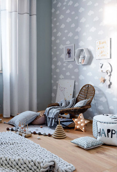 Reading nook in a baby blue cloud themed baby room for a boy.