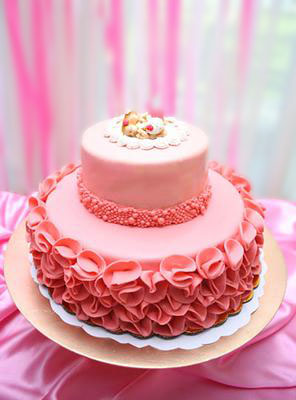 Homemade pink baby shower cake for twin girls with ruffles and homemade fondant sleeping baby cake topper.
