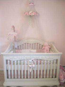 Elegant white baby girl crib with carved wood details and medallions