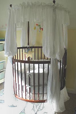 Yellow and white baby nursery decor with round crib and bedding collection