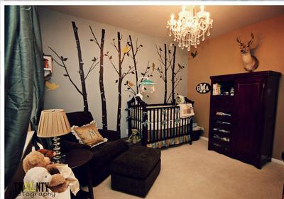 Woodland creatures decorate nursery walls in a baby boy's nursery filled with forest creatures
